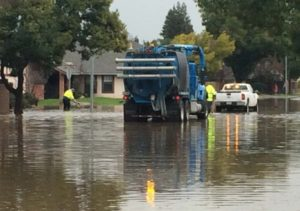 photo shows flooded road with utility workers trying to fix the issue.